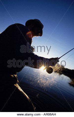 Man Flyfishing in Portage w/ Closeup of Reel Spinning AK Summer - Stock Photo