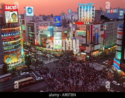 Pedestrians filling crosswalks in Shibuya district of Tokyo under sunset skies and neon lights of high rise facades - Stock Photo