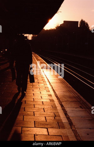 Silhouetted commuter on railroad platform - Stock Photo