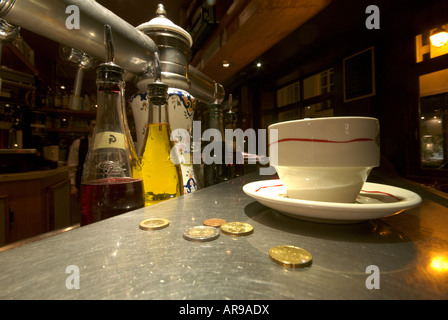 Cup of coffee and loose change on a typical zinc bar counter in Paris - Stock Photo