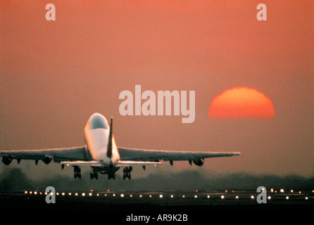airliner Boeing 747 jumbo jet airliner taking off at sunset sunrise dusk showing jet thrust exhaust - Stock Photo