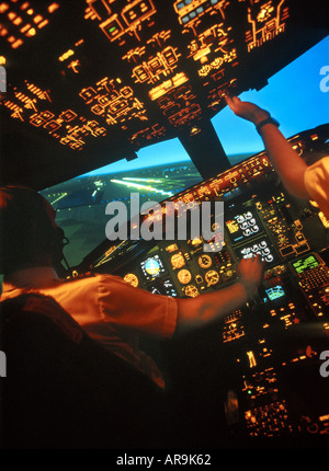 Boeing 757 jet airliner cockpit pilots at the controls on final approach to land with one engine failed - Stock Photo