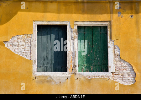Two shuttered windows with peeling paint set in stucco covered brick wall in need of repair and refurbishing Venice - Stock Photo