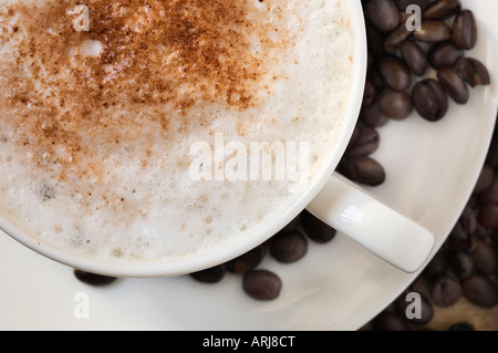 A close up of freshly made cup of Cappuccino coffee on a saucer, surrounded by roasted coffee beans - Stock Photo