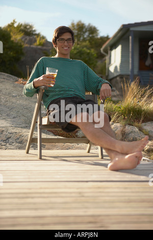 Young Man relaxing on Jetty - Stock Photo