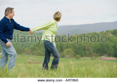 Mature couple walking in field - Stock Photo