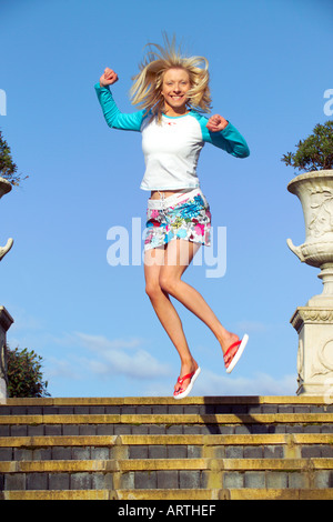 Young woman jumping on staircase, smiling - Stock Photo