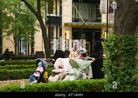 ILLINOIS Chicago Three observant Muslim women pushing strollers in Water Tower Park wearing burqas and head scarf - Stockfoto