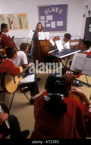 Multiracial group of  teenage students playing various instruments in music class with music books on stands - Stock Photo