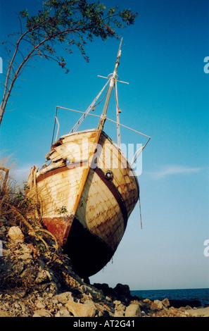 An old boat sitting on the rocks - Stock Photo