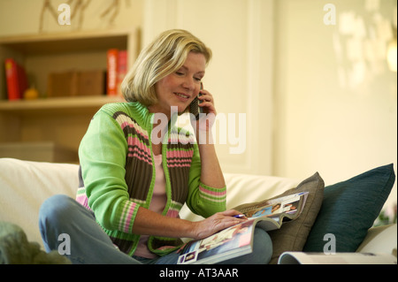 A woman placing an order with a mail order company on the telephone - Stock Photo