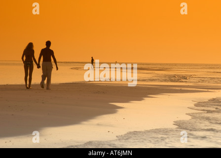 Couple on the beach, silhouetted at sunset, Maldives - Stock Photo