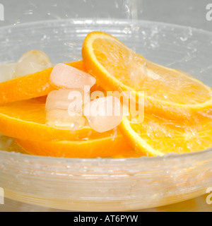 Slices of orange with ice cubes in bowl - Stock Photo