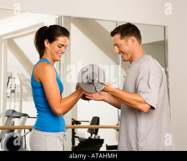 Man and woman lifting weights in gym - Stock Photo