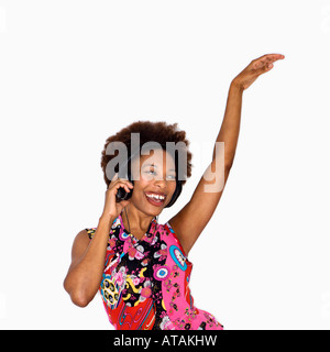 Woman with afro wearing vintage print fabric and listening to headphones smiling and dancing - Stock Photo