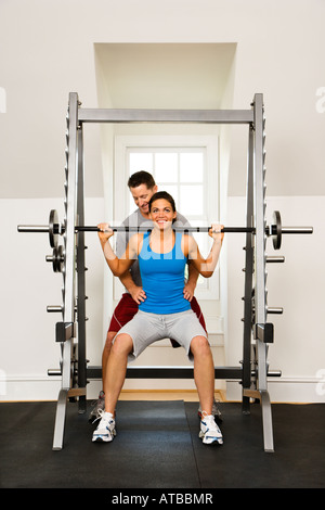 Woman lifting weights in gym being assisted by man - Stock Photo