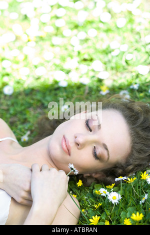 Young woman lying in on back on the ground, holding flower, eyes half-opened - Stock Photo