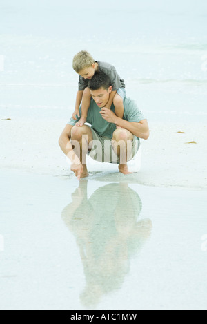 Man crouching at the beach, holding son on shoulders, pointing at shallow water - Stock Photo