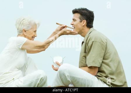 Senior woman feeding adult son takeout food with chopsticks, side view - Stockfoto