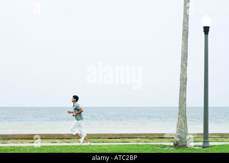 Man running at the beach, listening to headphones, side view - Stockfoto