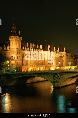 A view at night and from the opposite side of the Seine river of La Conciergerie a building on the Ile de Cite which - Stock Photo