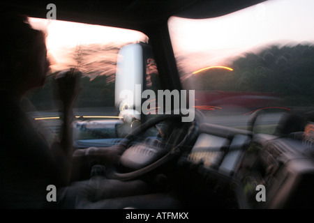 A young woman drives an eighteen-wheeler truck spends many hours on the road alone relies on CB radio for communication - Stock Photo