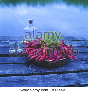 Crayfish in a bowl with a wine bottle and two glasses beside it - Stock Photo