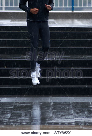 Man coming down steps in the rain - Stock Photo
