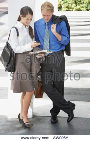 Two businesspeople outdoors looking at personal digital assistant - Stock Photo