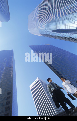 Businessman and woman under downtown Los Angeles skyscrapers - Stock Photo