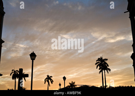 A crucifix and palms trees silhouetted against a Nicaraguan sunset - Stock Photo