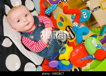 Horizontal portrait of a cute Caucasian baby girl lying on a colourful baby playgym mat to stimulate and develop - Stock Photo