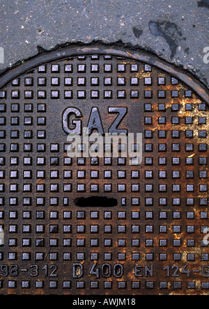 Gas type in French on man hole cover. - Stock Photo