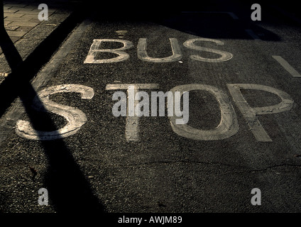 Bus Stop painted text on street. - Stock Photo