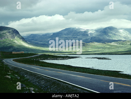 Sweden, road next to sea and mountains - Stock Photo