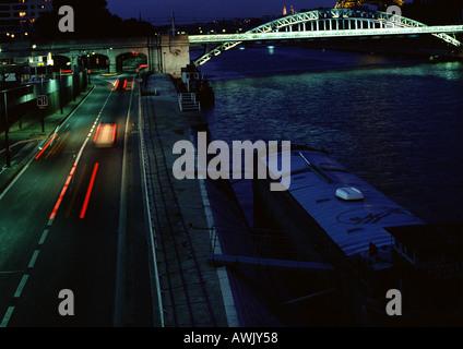 France, Paris, cars traveling on quai at night, blurry. - Stock Photo