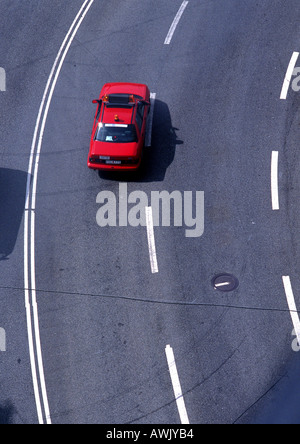 Red car on road with white lines, high angle view, full frame - Stock Photo