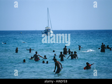 People wading in sea, sail boat in background - Stock Photo