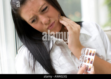 woman with toothache and pills - Stock Photo