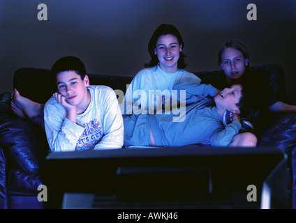 Young adults sitting together on couch watching television in the dark. - Stock Photo