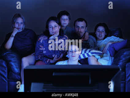 Family watching television together in the dark. - Stock Photo