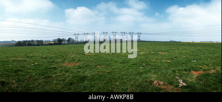 Rural field with row of power lines in the distance, France - Stock Photo