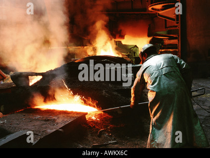Man bending forward, working in blast furnace, rear view - Stock Photo