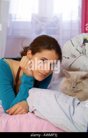 Young woman laying on bed with her cat - Stock Photo