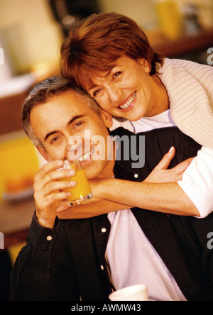 Woman hugging man from behind, man holding glass of juice, close up, portrait - Stock Photo