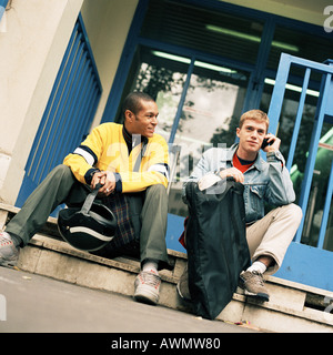 Young men sitting on steps with backpacks, one using cell phone. - Stock Photo