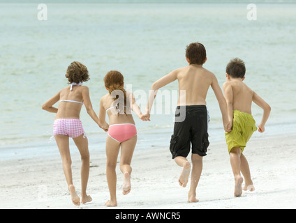 Four kids holding hands and running toward water, on beach, rear view - Stock Photo
