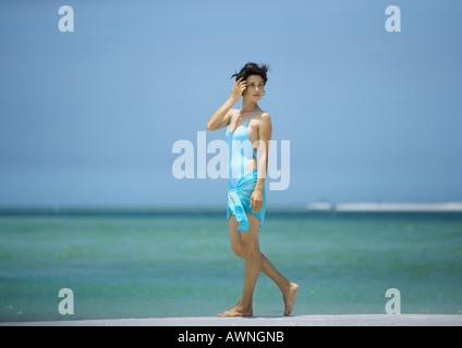 Woman walking on beach - Stockfoto