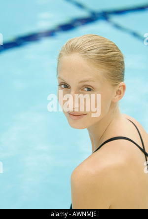 Woman by pool, looking over shoulder, smiling at camera - Stock Photo