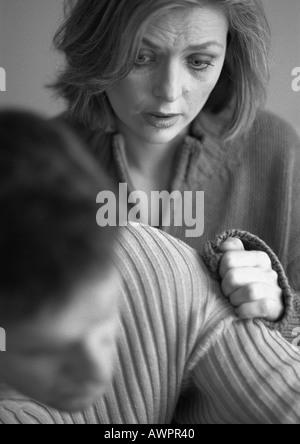 Woman touching man's arm, close-up, b&w - Stock Photo
